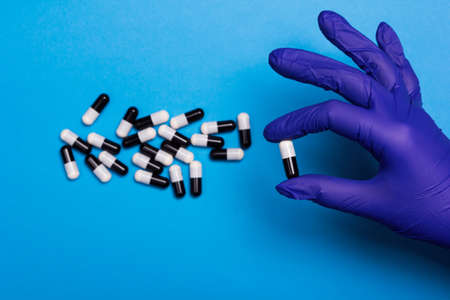 Photo pour Tablet capsule in hand and medechin glove. Black and white medicine on a blue background from the virus. Vitamin for immunity and health maintenance. - image libre de droit
