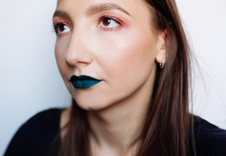 Photo pour Close up selfie portrait of pretty young brunette with creative make up: green ilpstick and red eyeshadows - image libre de droit