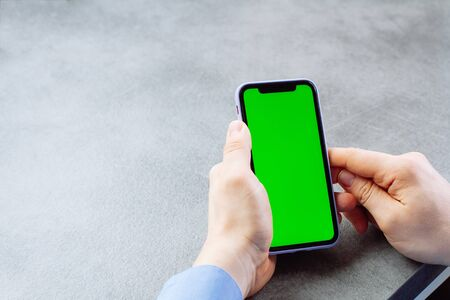 Photo pour Man touches and looks at the screen of the smartphone with a green screen. Chroma key on the screen of the telephone in businessman's hands on gray background - image libre de droit