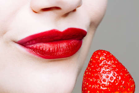 Photo pour Macro close up of caucasus woman's lips with red lipstick and fresh strawberry. Food pleasure, healthy food concept - image libre de droit