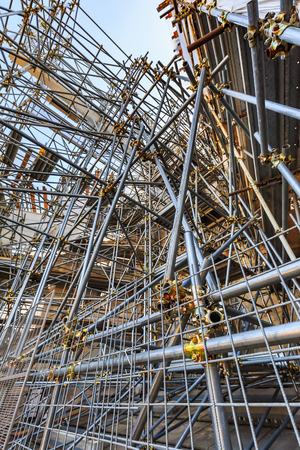 Scaffolding and steel pipes structure using scaffold clamps to fix them firmly for renovation work on the roof of Duomo di Milano, Italy