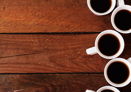 Wooden background with white cup of coffee