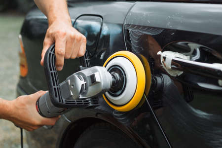 Photo pour Polishing a used car with an electrical orbital buffer or polisher - image libre de droit