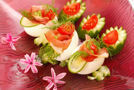 eggs stuffed with parma ham,cucumber,tomato and mayonnaise as appetizer for easter