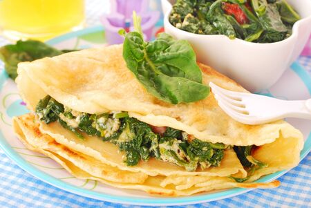 plate of pancake stuffed with spinach ,bacon and eggs for child