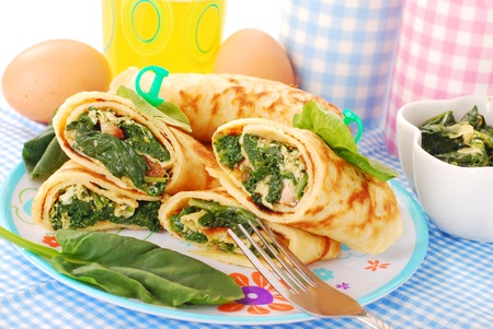 plate of rolled  pancakes stuffed with spinach ,bacon and eggs