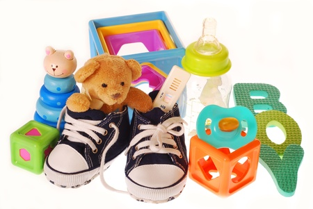 baby boy`s shoes with pregnancy ,teddy bear and toys isolated on white