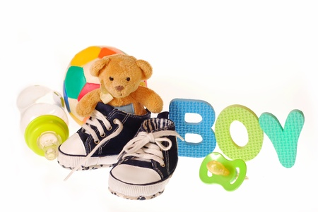 baby boy`s shoes with teddy bear ,stuffs and letters b,o,y isolated on white