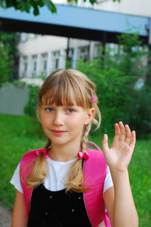 young girl going to school and waving hand for goodbye
