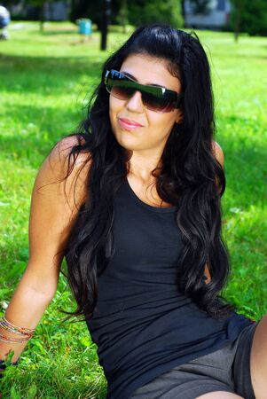 young beautiful brunette with sunglasses relaxing in the park, sitting on the grass
