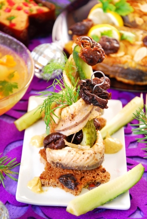 herring appetizer with prune and gherkin on christmas eve`s table