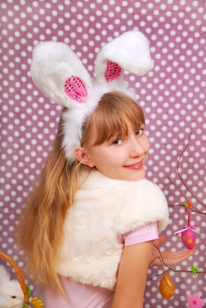 Easter bunny girl with funny ears on purple background with dotsの写真素材