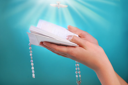 hands of a girl going to the first holy communion holding prayer book with rosary on blue background
