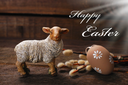 easter decoration with clay lamb figurine and egg on wooden background
