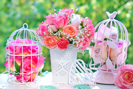 Foto de romantic style decoration with rose bouquet and metal cages in summer garden - Imagen libre de derechos