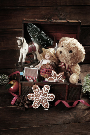 Vintage christmas toys like doll, teddy bear, rocking horse and decorations in old treasure chest on wooden background