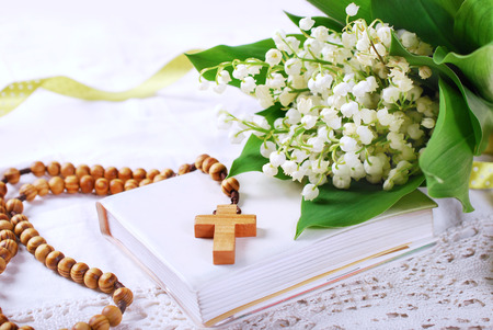 Photo for the first holy communion with wooden rosary,prayer  book and bunch of lily of the valley - Royalty Free Image