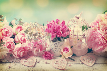 romantic vintage love background with bunches of roses, old cages and hearts