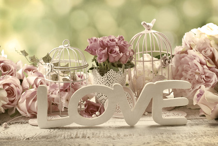 Photo for romantic vintage love background with bunches of roses, old cages and and wooden word - Royalty Free Image