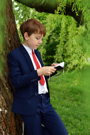 outdoor portrait of young boy in dark suit going to First Holy Communion