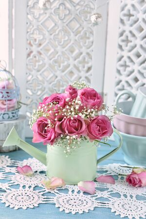 Photo for bunch of pink roses in a mint watering can in shabby chic style interior - Royalty Free Image
