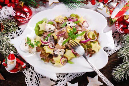Photo pour herring, potato, apple, onion and sour cream salad on fish shaped plate for Christmas - image libre de droit