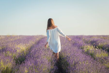 Photo pour Beautiful young woman in a white dress walks in the lavender field - image libre de droit
