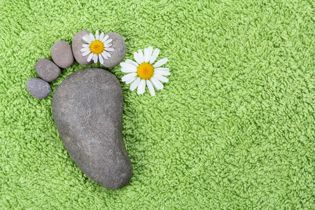 Foot with chamomile on green towel