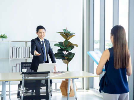Photo pour Asian businessman, boss in suit making hand gesture to invite young woman holding resume in the job interview to sit down on the chair near huge glass window in manager room in modern office interior. - image libre de droit