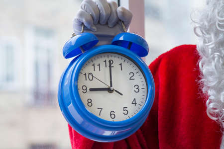 Santa's hand holding a blue alarm clock with time next to the window