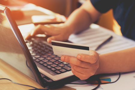 Photo pour woman hand holding credit card and using laptop computer. Online shopping concept - image libre de droit