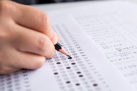 Photo pour Students hand holding pencil writing selected choice on answer sheets and Mathematics question sheets. students testing doing examination. school exam - image libre de droit