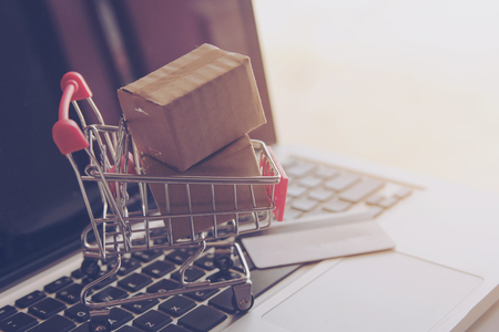 Foto de Shopping online concept - Shopping service on The online web. with payment by credit card and offers home delivery. parcel or Paper cartons with a shopping cart logo on a laptop keyboard - Imagen libre de derechos