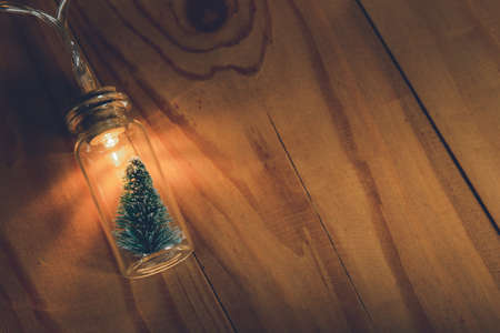 Photo for Light bulb and small Christmas tree in glass jar over wooden background - Royalty Free Image
