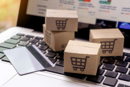 Photo for Online shopping - Paper cartons or parcel with a shopping cart logo and credit card on a laptop keyboard. Shopping service on The online web and offers home delivery. - Royalty Free Image