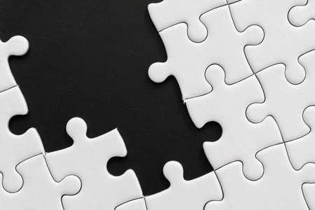 Photo pour Unfinished white jigsaw puzzle pieces on black background - image libre de droit