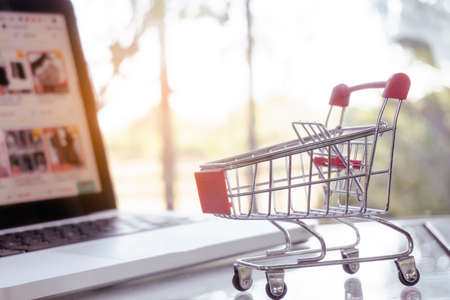 Photo pour Online shopping concept - shopping cart or trolley and laptop on table - image libre de droit