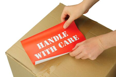 hands placing handle with care label on cardboard box