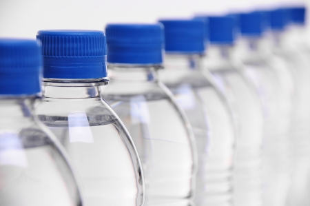 row of water bottle lids with select focus on second bottle
