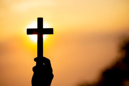Photo pour Silhouette off woman hands holding wooden cross on sunrise background, Crucifix, Symbol of Faith. - image libre de droit