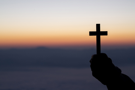 Photo for Silhouette of cross in human hand, the background is the sunrise., Concept for Christian, Christianity, Catholic religion, divine, heavenly, celestial or god. - Royalty Free Image