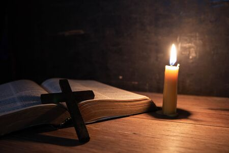 Photo for Cross with bible and candle on a old oak wooden table. Beautiful gold background. Religion concept. - Royalty Free Image
