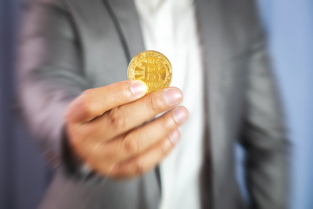 Businessman Holding Crypto Currency Coin, The Virtual Money Currency for the Future Economy and Commerce.