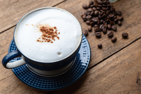 Photo pour Capucino Coffee with Coffee Beans on the Old Wood Table. - image libre de droit