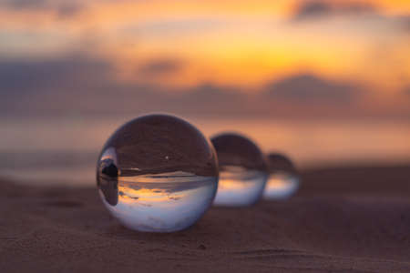Photo pour Three clear crystal balls of three sizes are sphere reveals  seascape view with spherical  placed on the sand at Karon Beach during sunset. - image libre de droit