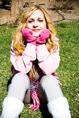 sheltered young girl sitting on the grass with pink accessories