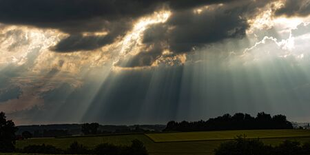 Photo for sunrays in the sky with dramatic black thunderclouds - Royalty Free Image
