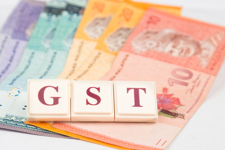 Concept - GST word against Malaysian Ringgit notes as  backdrop