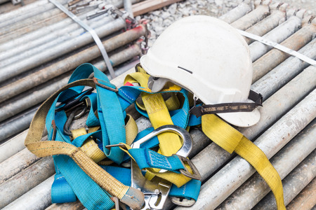 Foto de Safety helmet and harness at construction site - Imagen libre de derechos