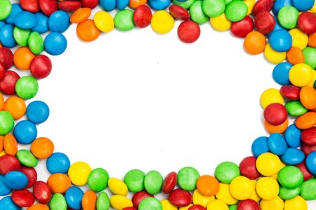 Frame of colorful chocolate candy on white background with space for text
